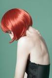 Stående av en ung härlig flicka med rött kort hår i studion på en grön bakgrund Royaltyfri Foto