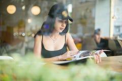 Stående av en ung härlig flicka som bara sitter i ett kafé och ett r fotografering för bildbyråer