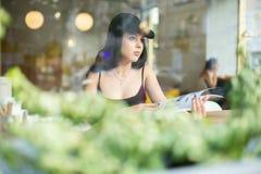 Stående av en ung härlig flicka som bara sitter i ett kafé och ett r arkivfoton