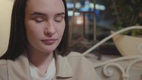 Stående av en ung härlig flicka som hänsynsfullt sitter i aftonen på en terrass i ett kafé eller en restaurang stock video