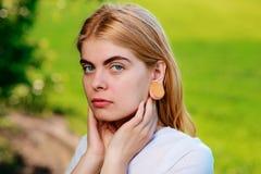 Stående av en ung härlig kvinna med trätunneler i hennes e royaltyfri foto