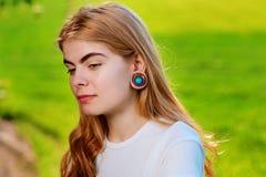 Stående av en ung härlig kvinna med trätunneler i hennes e arkivfoto