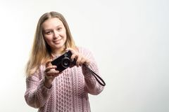 Stående av en ung härlig le bärande gräns för blond flicka - rosa färg stucken tröja med en tappningkamera i henne händer arkivbild