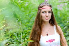 Stående av en ung härlig slavisk flicka med långt hår och den slaviska etniska klänningen i busksnår av högväxt gräs Arkivbild