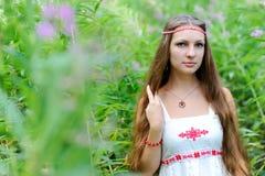 Stående av en ung härlig slavisk flicka med långt hår och den slaviska etniska klänningen i busksnår av högväxt gräs Arkivfoton
