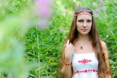 Stående av en ung härlig slavisk flicka med långt hår och den slaviska etniska klänningen i busksnår av högväxt gräs Arkivbilder