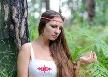 Stående av en ung härlig slavisk flicka med långt hår och den slaviska etniska klänningen i en sommarskog Arkivfoto