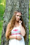 Stående av en ung härlig slavisk flicka med långt hår och den slaviska etniska klänningen i en sommarskog Fotografering för Bildbyråer