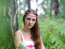 Stående av en ung härlig slavisk flicka med långt hår och den slaviska etniska klänningen i en sommarskog Royaltyfri Bild