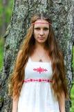 Stående av en ung härlig slavisk flicka med långt hår och den slaviska etniska klänningen i en sommarskog Royaltyfri Foto