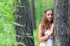 Stående av en ung härlig slavisk flicka med långt hår och den slaviska etniska klänningen i en sommarskog Royaltyfria Bilder