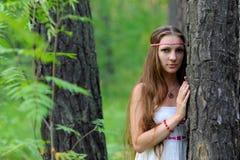 Stående av en ung härlig slavisk flicka med långt hår och den slaviska etniska klänningen i en sommarskog Arkivbild