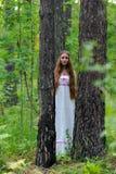 Stående av en ung härlig slavisk flicka med långt hår och den slaviska etniska klänningen i en sommarskog Royaltyfri Fotografi