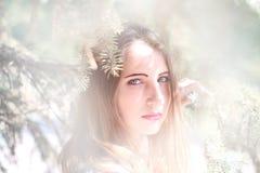 Stående av en ung kvinna i de prydliga filialerna Royaltyfri Foto
