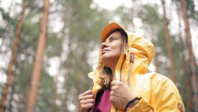 Stående av en ung kvinna i ett ljust anseende för gult omslag på den regniga skogen lager videofilmer