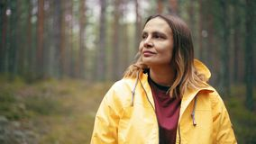 Stående av en ung kvinna i ett ljust anseende för gult omslag på den regniga skogen stock video