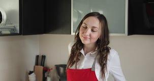 Stående av en ung kvinna i ett rött förkläde i köket lager videofilmer
