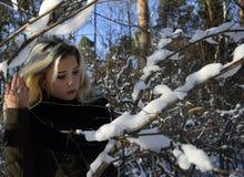 Stående av en ung kvinna i en snöig skog royaltyfri bild