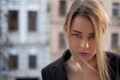 Stående av en ung kvinna i en svart dräktnärbild mot en bakgrund av en oskarp stad i strålarna av inställningssolen royaltyfri fotografi