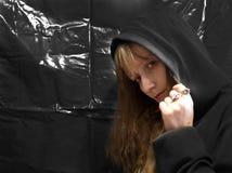 Stående av en ung kvinna i en svart huv på en svart bakgrund royaltyfria foton