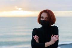Stående av en ung kvinna i en svart tröja i kallt väder mot bakgrunden av havet och himlen på solnedgången arkivfoto