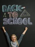 Stående av en ung kvinna, lärare framme av en svart tavla Arkivbild