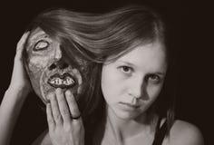 Stående av en ung kvinna med den spöklika sceniska maskeringen Arkivfoton