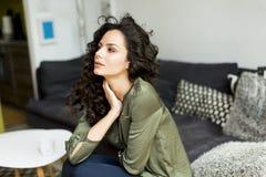 Stående av en ung kvinna med lockigt hår som kopplar av på en soffa arkivbilder