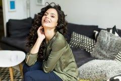 Stående av en ung kvinna med lockigt hår som kopplar av på en soffa arkivfoton