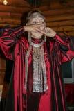 Stående av en ung kvinna som bär den nationella klänningen och spelar det nationella musikinstrumentet arkivfoto