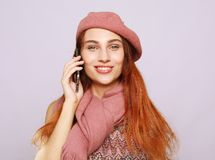 Stående av en ung kvinna som bär den rosa dräkten som talar på mobiltelefonen arkivfoton