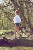Stående av en ung kvinna som balanserar på den stupade trädstammen över ström arkivbilder