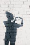 Stående av en ung kvinna som bildar en hjärta med henne händer royaltyfri bild