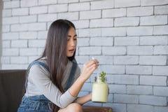 Stående av en ung kvinna som dricker en coctail Arkivbild