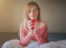 Stående av en ung kvinna som dricker kaffeiin sängen Royaltyfria Foton