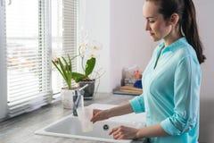 Stående av en ung kvinna som framme vinner ett exponeringsglas av rent klappvatten i köket av fönstret fotografering för bildbyråer