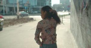 Stående av en ung kvinna som går i stadsgatorna