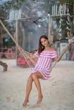 Stående av en ung kvinna som poserar i en hängmatta på bakgrunden av det kust- lägret arkivfoto