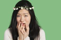 Stående av en ung kvinna som uttrycker skräck och ångest över grön bakgrund Royaltyfria Foton