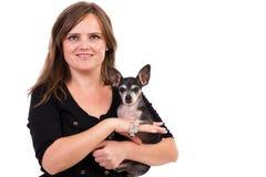 Stående av en ung kvinnaholding henne älsklings- hund. Arkivfoton