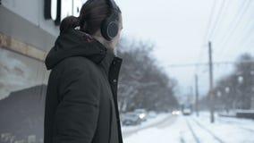 Stående av en ung långhårig man med ett skägg i hörlurar som står på ett spårvagnstopp i vinter och väntar på en spårvagn lager videofilmer
