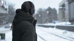 Stående av en ung långhårig man med ett skägg i hörlurar som står på ett spårvagnstopp i vinter och väntar på en spårvagn arkivfilmer