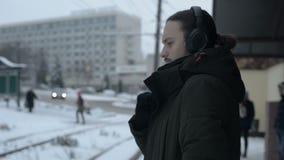 Stående av en ung långhårig man med ett skägg i hörlurar som står på ett spårvagnstopp i vinter och väntar på en spårvagn stock video