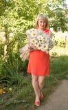 Stående av en ung le kvinna i den röda klänningen på en natur royaltyfri foto
