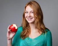 Stående av en ung ljust rödbrun kvinna i grön blus med biten app arkivbild