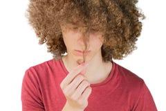 Stående av en ung lockig europeisk man som worriedly ser på hans långa hår rymmer en krullning av hår med hans fingrar mycket fro fotografering för bildbyråer