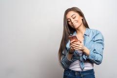 Stående av en ung lycklig le flicka som rymmer hennes rosa smartphone och läsning eller håller ögonen på något på den royaltyfri bild