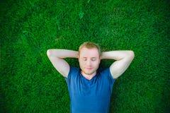Stående av en ung lycklig man med stängda ögon som kopplar av på gräset med hans händer under huvudet Selektivt fokusera Arkivfoton