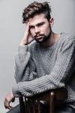 Stående av en ung man i grå sweater Huvudvärk arkivfoton