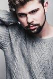 Stående av en ung man i grå sweater Huvudvärk royaltyfri foto